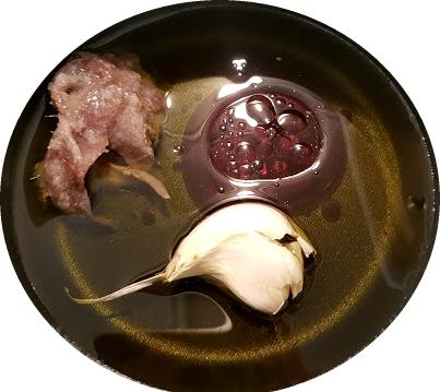 Olio, aceto, acciughe e aglio per preparare la salsa di condimento